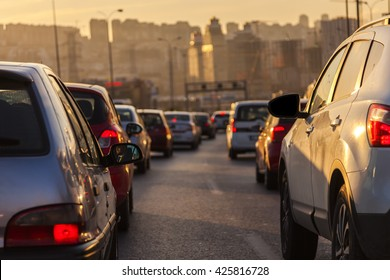 Evening traffic. Drivers who wait in traffic to go home from work at the end of the day. The evening sun is reflected over the cars.  A close-up view of cars. It goes a way between high buildings.