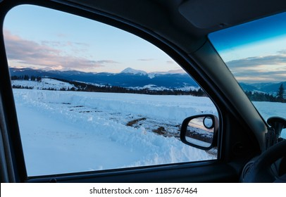 Evening twilight winter Chornohora mountain ridge scenery view through car windshield (Ukraine, Carpathian Mountains, Hoverla, Petros and other alps from Yablunytsia pass). Car model unrecognizable.
