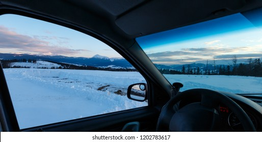 Evening twilight winter Chornohora mountain ridge scenery view thru car windshield, Ukraine, Carpathian Mountains. Beautiful vacation travel by car concept. Car model unrecognizable.