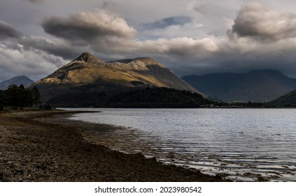Evening view across bright water of Loch Leven to the sunlit Pap of Glencoe with the mountains at the western end of Glencoe in shadow under low cloud.