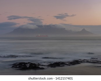 Evening view Cape Town, Table Mountain, Devil's Peak and Lion's Head with a ship in Table Bay from Blouberg. Cape Town . Western Cape. South Africa