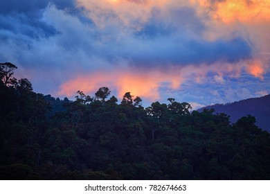 Evening view of the Costa Rican mountains, Cerro de la Muerte with a volcano in the clouds, illuminated by the setting sun. Mountain landascape. Los Quetzales National Park Nature Reserve. Costa rica.