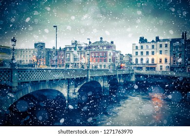 Evening view of Dublin Ireland at the Grattan Bridge of the River Liffey with snowflakes falling during winter snow storm