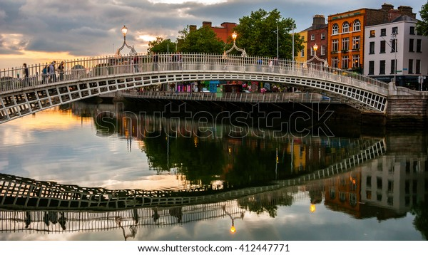 Evening view of famous Ha Penny Bridge in Dublin, Ireland at sunset