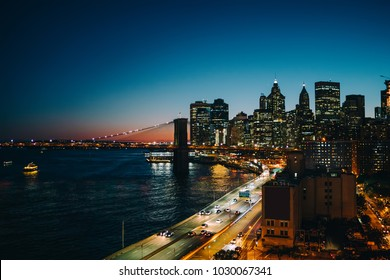 Evening view of financial district of megalopolis with modern architecture near river, New York cityscape with developed infrastructure with skyscrapers bridges and rush traffic on highway in downtown
