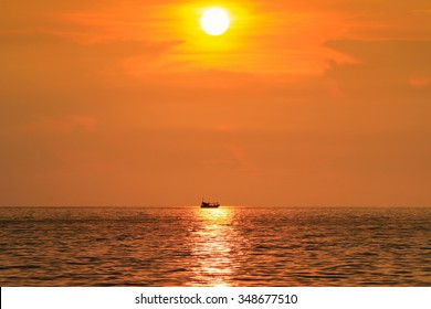 Evening view of golden sunset photo with a silhouette of a boat floating on the sun reflection