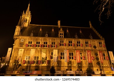 Evening view of the ice skating rink around the medieval town hall with a lot of advertising flags and lights. Gouda, the Netherlands.