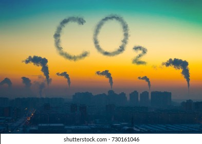 Evening view of the industrial landscape of the city with smoke emissions from chimneys at sunset. Inscription CO2