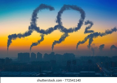 Evening view of the industrial landscape of the city with smoke emissions from chimneys at sunset CO2