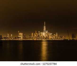 Evening view of lower New York City financial district shot from the Hoboken Terminal. Reflections visible on the Hudson River.
