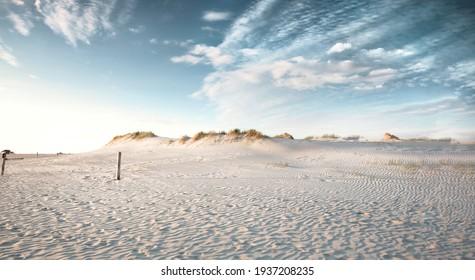 Abends Blick auf kleine Sanddüne mit grünem Gras. Sandstrand an der Küste. Blauer Himmel mit weißen Wolken. Sonnenuntergang.