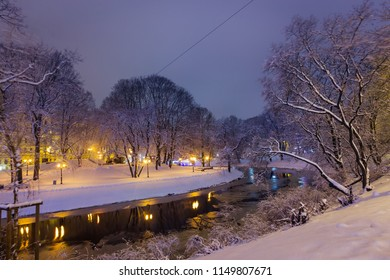 An evening view on a snow covered park and a river in Riga, Latvia