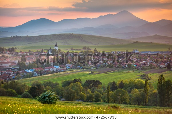 An evening view on the village with flowery meadow. Sunset over the hills. Sunset over the mountains. View of the Slovak countryside.