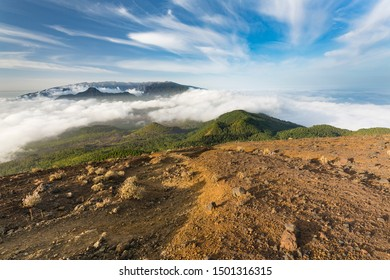 Evening view over the mountains of La Palma with trade wind clouds passing over the Cumbre Nueva. Seen from the top of the volcano Birigoyo.