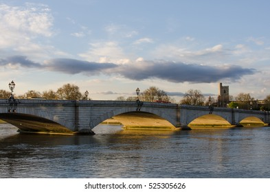 An evening view of Putney bridge in London with golden light lit the arches of the bridge