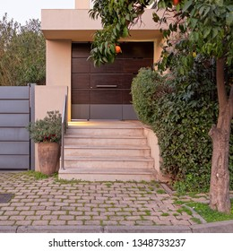 evening view of sidewalk by elegant house entrance stairs and door, with potted plant and orange tree