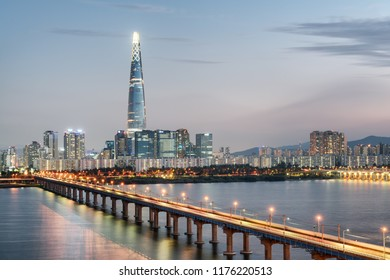 Evening view of skyscraper at downtown of Seoul in South Korea. Scenic modern tower and Jamsil Railway Bridge over the Han River (Hangang) at sunset. Wonderful cityscape.