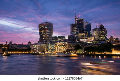 Evening view of the skyscrapers in the City, a financial district in London, United Kingdom, with the River Thames