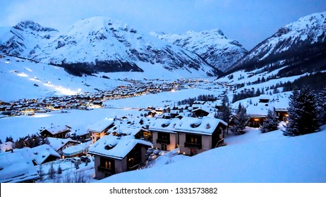 Evening view to a small Italian village in  the Alps. Small apartments with lights in windows create beautiful athmposphere like in a fairy tale. Ski resort Livigno during the winter season.