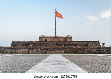 Evening view of a square and the flag of Vietnam (red flag with a gold star) fluttering over a tower of the Citadel on blue sky background in Hue, Vietnam. Within the Citadel is the Imperial City.