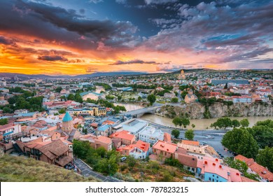 Evening View Of Tbilisi At Colorful Sunset, Georgia. Summer Cityscape. On Photograph Visible The Bridge Of Peace, A New Concert Hall, Holy Trinity Cathedral Of Tbilisi, Metekhi Church