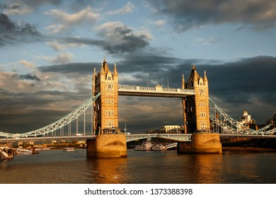 Evening view of Tower Bridge at sunset over dramatic cloudy sky. Thames River water reflection present.
