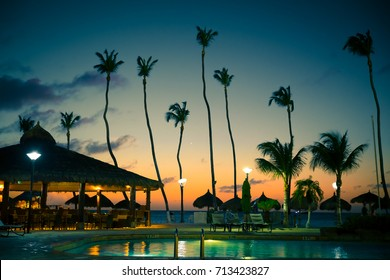 Evening view of tropical resort with tall palm trees, swimming pool, palapa huts, beach bar, ocean and sunset.