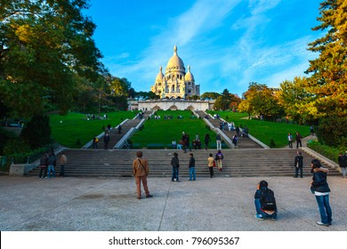 Evening views of Montmartre and  the Sacre-Coeur basilica in Paris, France. Tourists on the green grass lawns hillside of Montmartre. Blurred, unrecognizable faces.