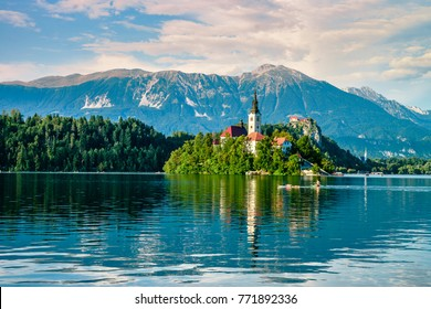 Evening views on the lake Bled with the famous Pilgrimage Church of the Assumption of Maria and Bled Castle and Julian Alps at background
