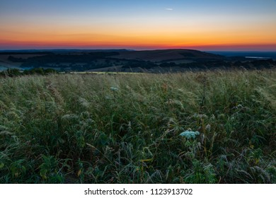 An evening walk over Willingdon Hill on the south downs near Eastbourne east Sussex south east England.  To catch a sunset and moon rising