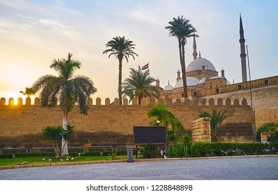 The evening walk at the Saladin Citadel with a view on sunset sky and the towering Alabaster (Muhammad Ali) Mosque behind the tall palm trees, Cairo, Egypt.