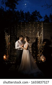 evening wedding ceremony. The couple is hugging. The moon shines in the night sky