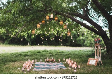 Evening wedding ceremony with a rug and lot of vintage lamps and candles on big tree. Rustic style