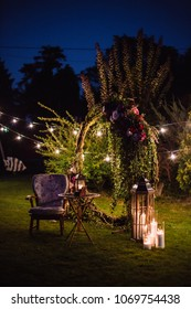 Evening wedding photo zone with an arch and armchair