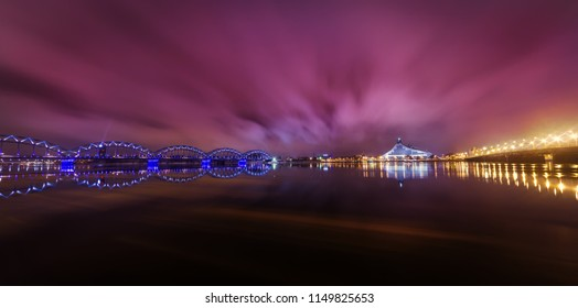 An evening winter view on the Daugava river and two bridges in Riga, Latvia