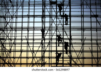 evening, the workers are climbing the silhouette of scaffolding in the high altitude, horizontal and vertical scaffolding formed a myriad of grid, industrial and modern urban construction background.