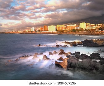 Eveningview of Puerto de la Cruz  Tenerife, with  the Atlantic  and purple  clouds.  In the foreground, the Atlantic  as the main theme,  volcanic rocks in the foreground with  waves.