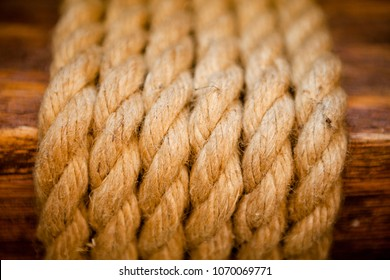 evenly wound thick ropes on a wooden background.
