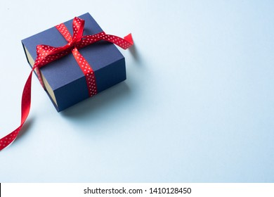event design concept - perspective view of fathers day layout with ribbon kraft gift box on blue background, copy space for mock up