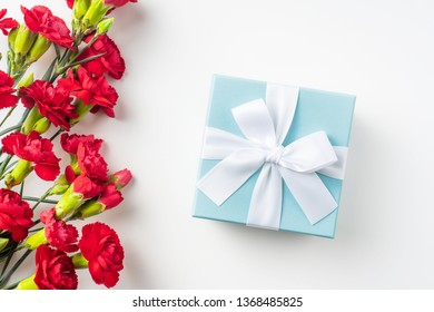 event design concept - top view of a bunch of red carnation and gift box isolated on white background for mothers day and valentines day, wedding event with copy space for mock up