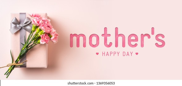 event design concept - top view of a bunch of pink carnation with gift box and greeting word on pink background for mothers day event with copy space for mock up