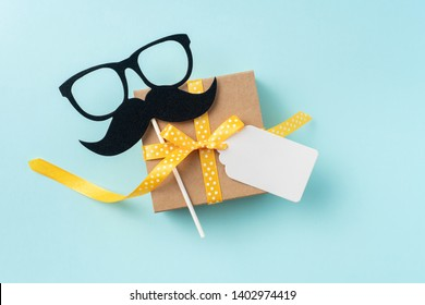 event design concept - top view of fathers day layout with yellow ribbon gift box, blank label, silhouette of eye glasses and beard, copy space for mock up