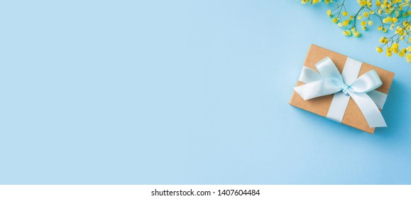 event design concept - top view of fathers day layout with ribbon kraft gift box, yellow flower on blue background, copy space for mock up