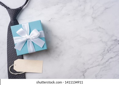 event design concept - top view of fathers day layout with kraft gift box and necktie on white wooden background, copy space for mock up