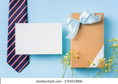 event design concept - top view of fathers day layout with ribbon kraft gift box, yellow flower and necktie on blue background, copy space for mock up