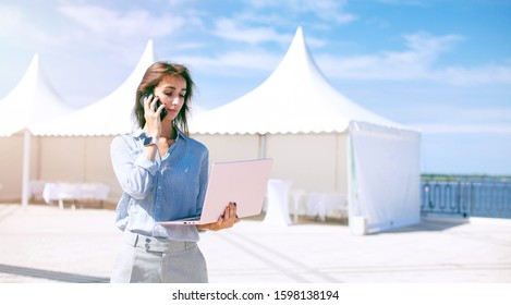 Event manager portrait. Preparation for public exhibition and global business expo. Young serious woman stand and work with her laptop near the Mobile tents. Installation of Exhibition Pavilions.
