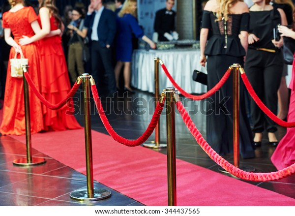event party. red carpet entrance with golden stanchions and ropes. guests in the background