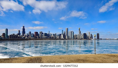 The ever growing skyline of downtown Chicago along a frozen Lake Michigan in the winter.