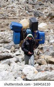EVEREST REGION,NEPAL- APRIL 23:Unidentified sherpa  carry heavy load in the Himalaya at Everest Base Camp trek on April 23,2013 in Everest region,Nepal.Sherpas are elite mountaineers in Himalayas.