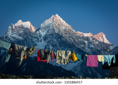 Everest trekking. In the frame, the dried laundry on the rope and part of the fence is blurred, the mountain in the background is in focus. Sunset. Nepal. Renjo la pass